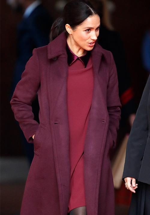 Meghan rugged up wearing a burgundy Club Monaco dress and coat as she attended an event in London. *(Image: Getty)*