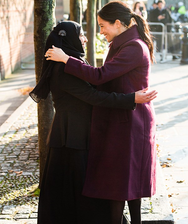 Meghan shared a sweet embrace with a woman involved in the charity cookbook. *(Image: Getty)*