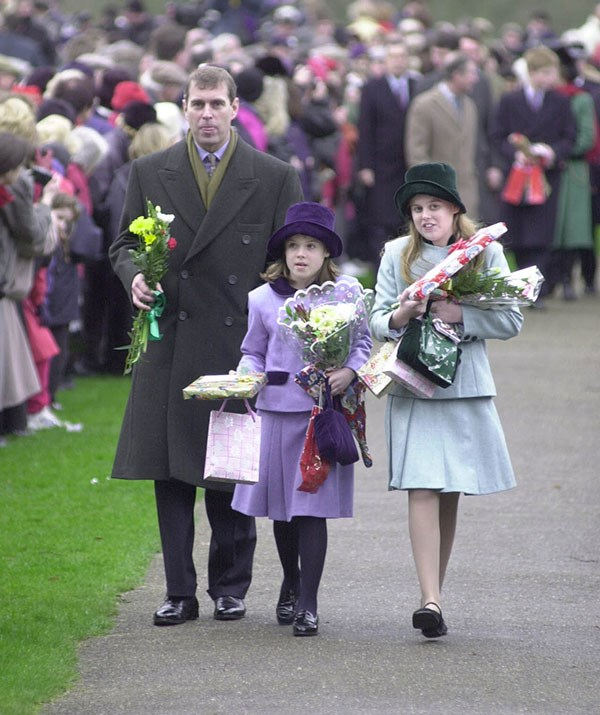 Interacting with royal fans walking to and from Christmas service is an annual tradition for the royal family. This particular year in 1999 Princess Eugenie and her sister were inundated with bouquets and presents. *(Image: Getty)*