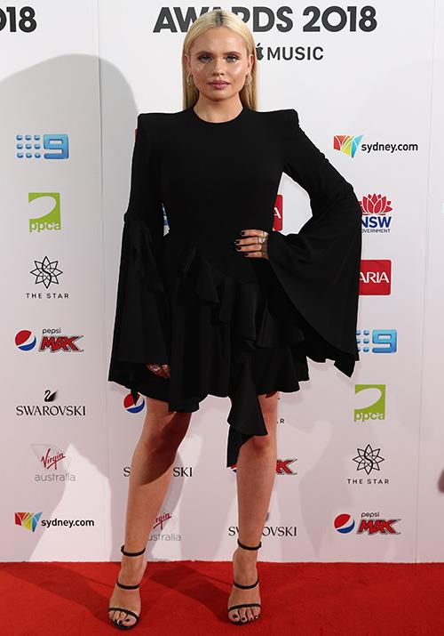 Singer Ali Simpson opts for a chic black dress with a dramatic flared sleeve. *(Image: Getty)*