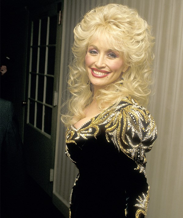 Pictured here in the 1980s, Parton embraced the bold trends of the decade in all its glory. *(Image: Getty)*