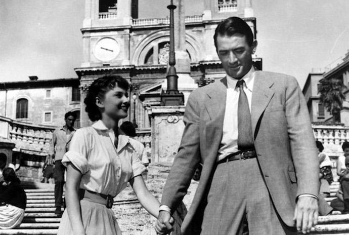 **ROMAN HOLIDAY (1953)** <br><br> During a European tour, Princess Ann (Audrey Hepburn) sneaks off for a night of adventure while visiting Rome. When a series of events leads her to American Reporter Joe (Gregory Peck), romance blossoms. However Joe's intentions may not be as pure as Ann's.
