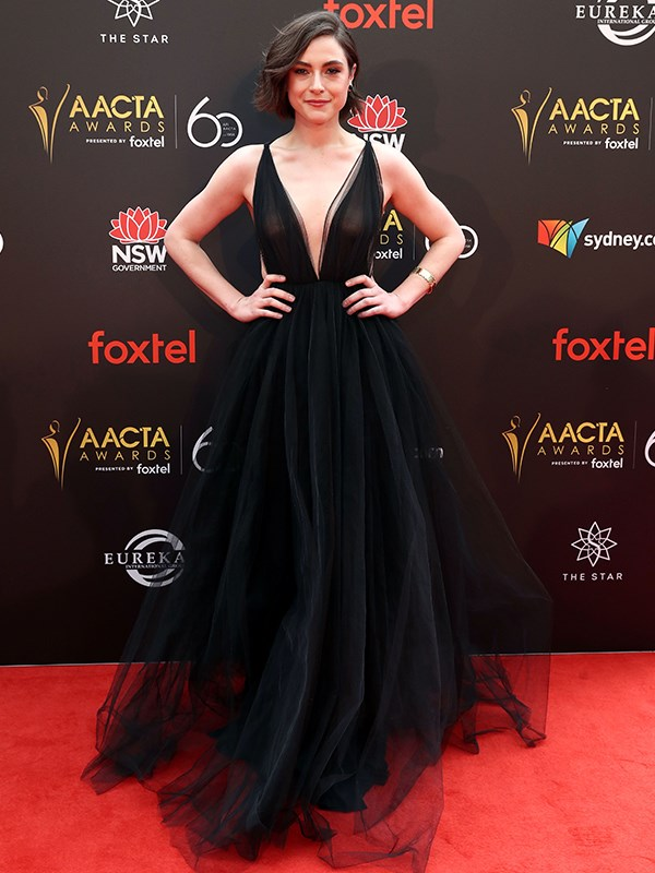 Actress Kate Cheel stuns in this plunging black frock with a dramatic tulle train. *(Image: Getty)*