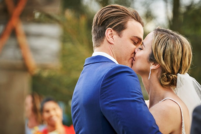 The newlyweds celebrate their marriage with a passionate kiss.
