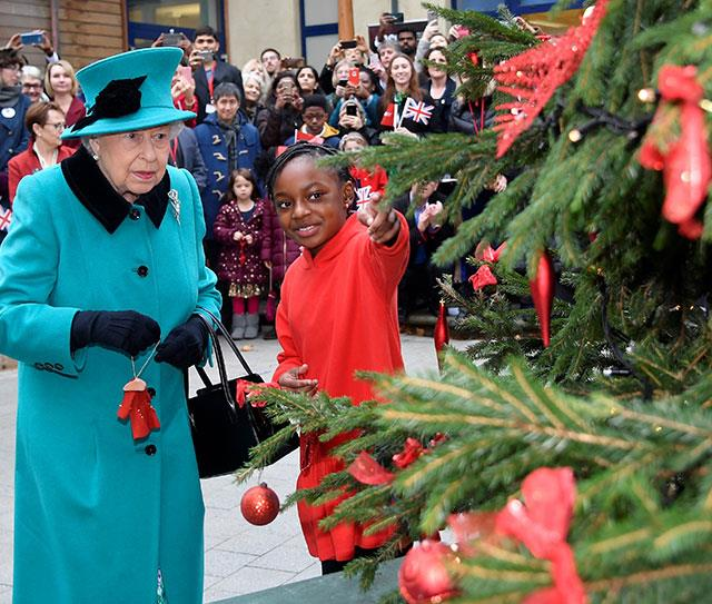 We love the look of concentration on Her Majesty's face. This is someone who doesn't take tree decoration lightly! *(Image: Getty)*
