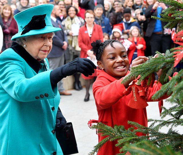 Imagine getting to decorate a Christmas tree with The Queen! That dream came true for eight-year-old Shylah Gordon when the pair hung baubles at the opening of Coram's new children's centre in London on December 5th. *(Image: Getty)*