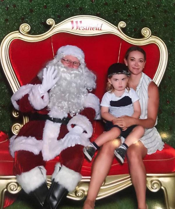 "Fitness guru [Michelle Bridges](https://www.nowtolove.com.au/tags/michelle-bridges|target=""_blank"") seems pretty stoked to visit Santa but her son Axel, who turns three on December 19th, isn't so sure about the bearded man in the red suit. *(Image: @mishbridges Instagram)*"