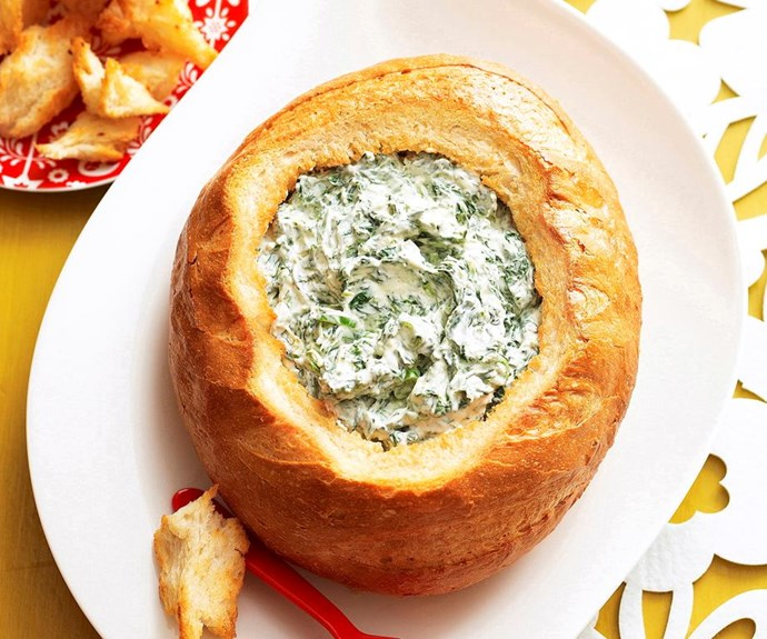 """**Cob spinach loaf** <br><br> This is one retro recipe that never goes out of style. The cheesy spinach dip has just the right amount of garlic and bacon bits to make this an instant hit at any party. <br><br> See the full *Australian Women's Weekly* recipe [here](https://www.womensweeklyfood.com.au/recipes/cob-loaf-spinach-dip-6574
