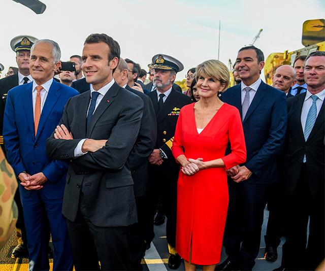 She'd stand out from the crowd in any colour, but this bright red ensemble looks strong and prominent on Julie as she stands with French President Emmanuel Macron. *(Image: Getty)*