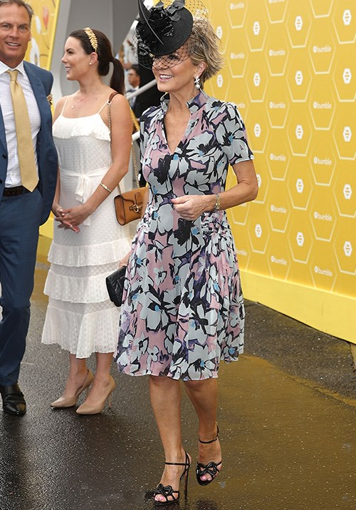 Heavy rain didn't put a damper on Bishop's parade at the 2018 Melbourne Cup - she looked flawless in her printed frock paired with a black fascinator. *(Image: Getty)*