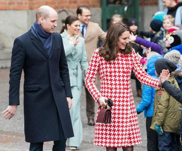 Kate also wore a bright red and white Catherine Walker houndstooth coat during her visit to Sweden in February - that's one way to keep her baby bump snug! *(Image: Getty)*