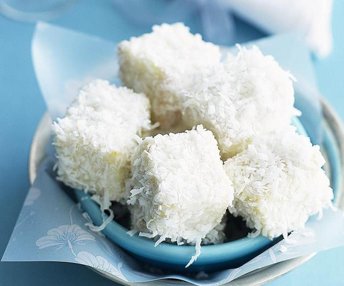 """**Little white lamingtons** <br><br> If you're looking for a new twist on an old favourite, these little white chocolate lamingtons are the business. Bite-sized pieces of feather-light sponge, dipped in white chocolate and coated in moist shredded coconut. <br><br> See the full *Australian Women's Weekly* recipe [here.](https://www.womensweeklyfood.com.au/recipes/little-white-lamingtons-8938 target=""""_blank"""")"""