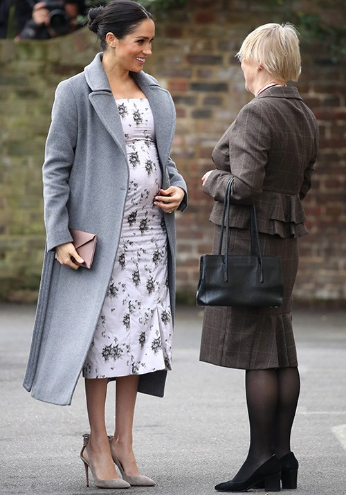Now that's a baby bump! Duchess Meghan stepped out on December 18 to visit a nursing home in Twickenham looking positively radiant. Her white floral dress by LA designer Brock Collection looked stunning paired with a grey woollen coat by Soia & Kyo. *(Image: Getty Images)*