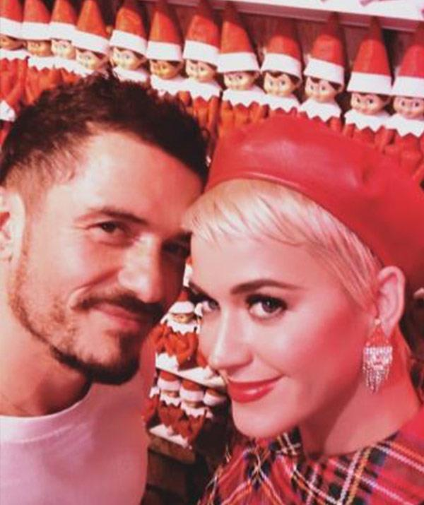 "A very loved-up Orlando Bloom and Katy Perry pose in front of an entire brigade of [elves on shelves.](https://www.nowtolove.com.au/christmas/christmas-food/elf-on-the-shelf-52796|target=""_blank"") *(Image: @katyperry Instagram)*"
