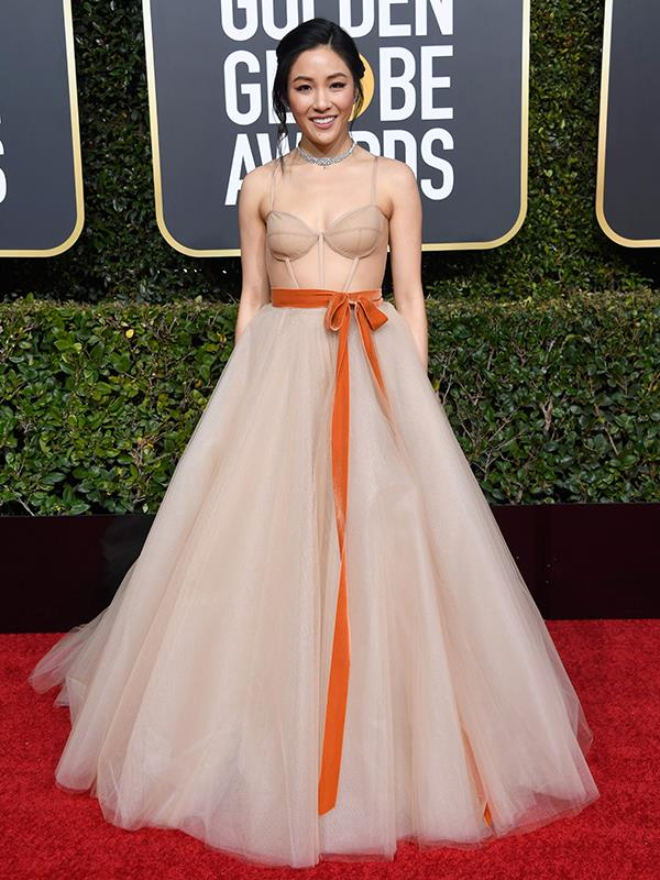 *Crazy Rich Asians* star Constance Wu is a vision in nude and orange velvet bow. This is her first nomination for her role in the film opposite Henry Golding.