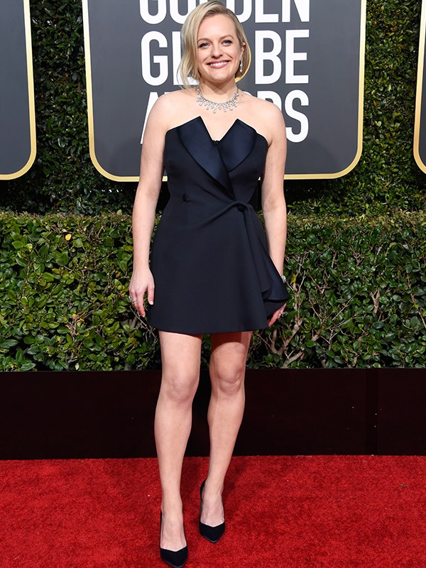 *The Handmaid's Tale* star Elisabeth Moss has opted for a short tuxedo dress as she walks the red carpet. She is nominated for Best Actress in a Television series for her role in the show.