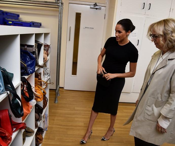 Duchess Meghan assists a women with choosing a handbag. *(Source: Getty)*