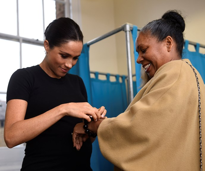 Duchess Meghan assists a woman with her bracelet, which she helped pick out. *(Source: Getty)*