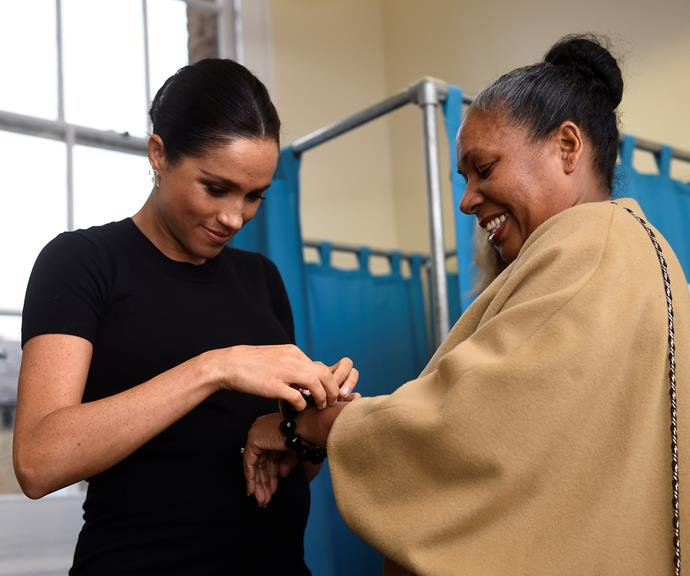 Duchess Meghan assists a woman with her bracelet, she helped pick out. *(Source: Getty)*