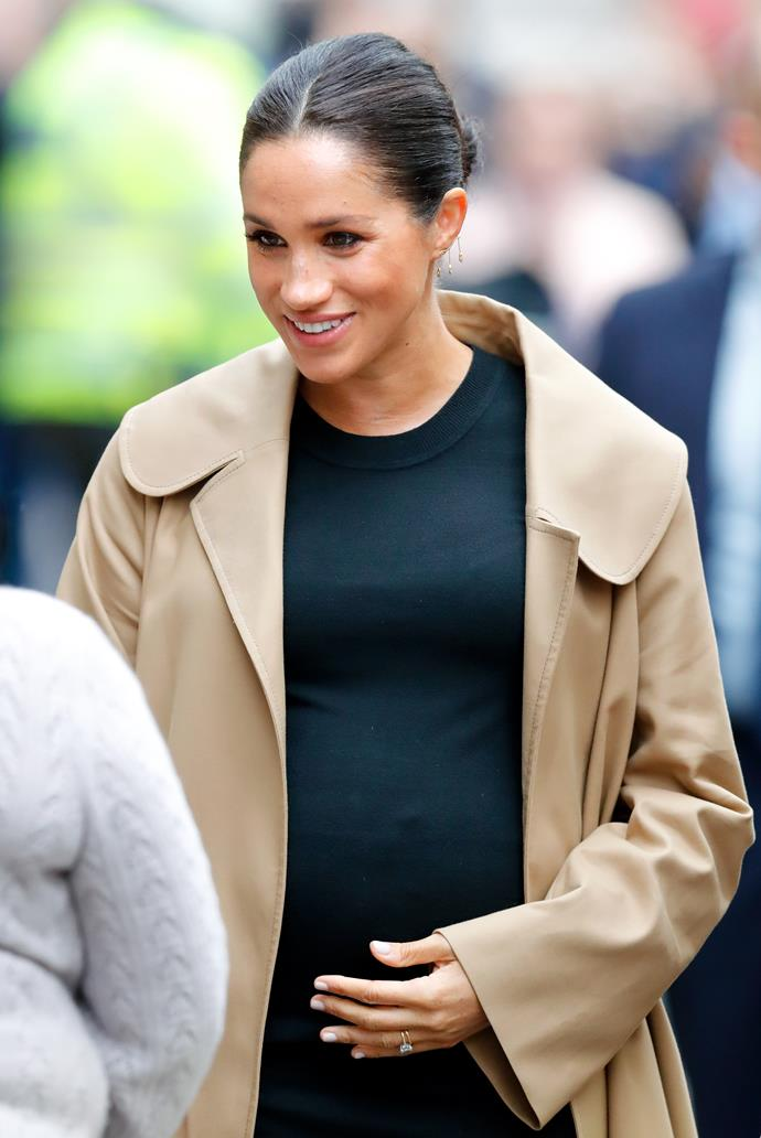 The Duchess places a protective hand over her bump. *(Image: Getty)*
