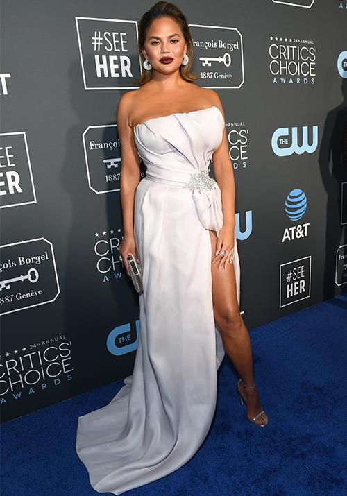 The ever stylish and sassy Chrissy Teigen knocked it out of the park once again showing off her voluptuous figure in this silver dress. *(Image: Getty)*