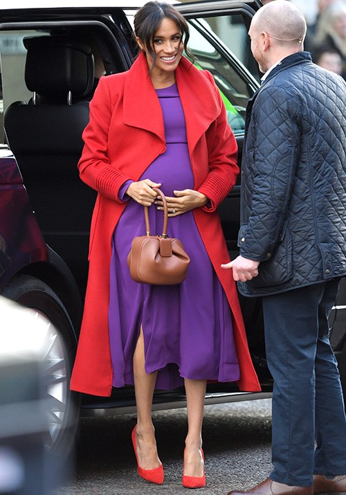 With her baby bump on show, Meghan looked stunning in purple Babaton by Aritizia dress paired with a red wrap coat by designer Sentaler. *(Image: Getty Images)*