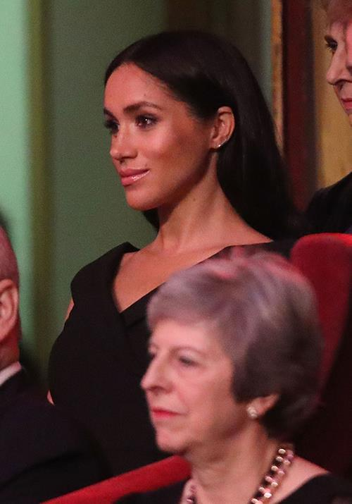Meghan's stunning black off-shoulder had us thinking it was another pricey designer piece. *(Image: Getty)*
