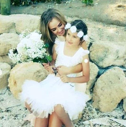 Flower girl Scout cuddles up to her mum. *(Image: @jay.may.ray Instagram)*