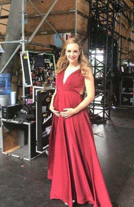 Ravishing in red, Penny and her bump stun in a gown by Jadore Evening. *(Image @penny.mcnamee Instagram)*