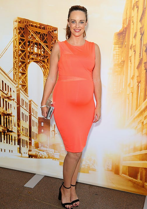 The actress turns head in this chic, bodycon orange dress. *(Image: Getty)*