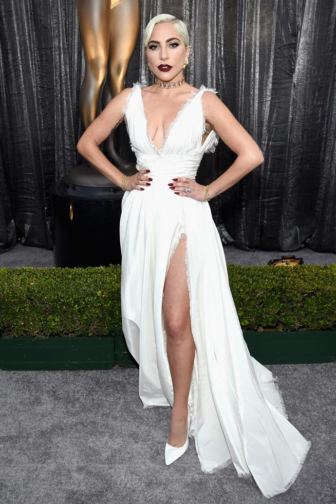 It's not a red carpet until Lady Gaga arrives and the Best Actress nominee is totally bringing it in this showstopping white dress, featuring a thigh-high split and plunging neckline.