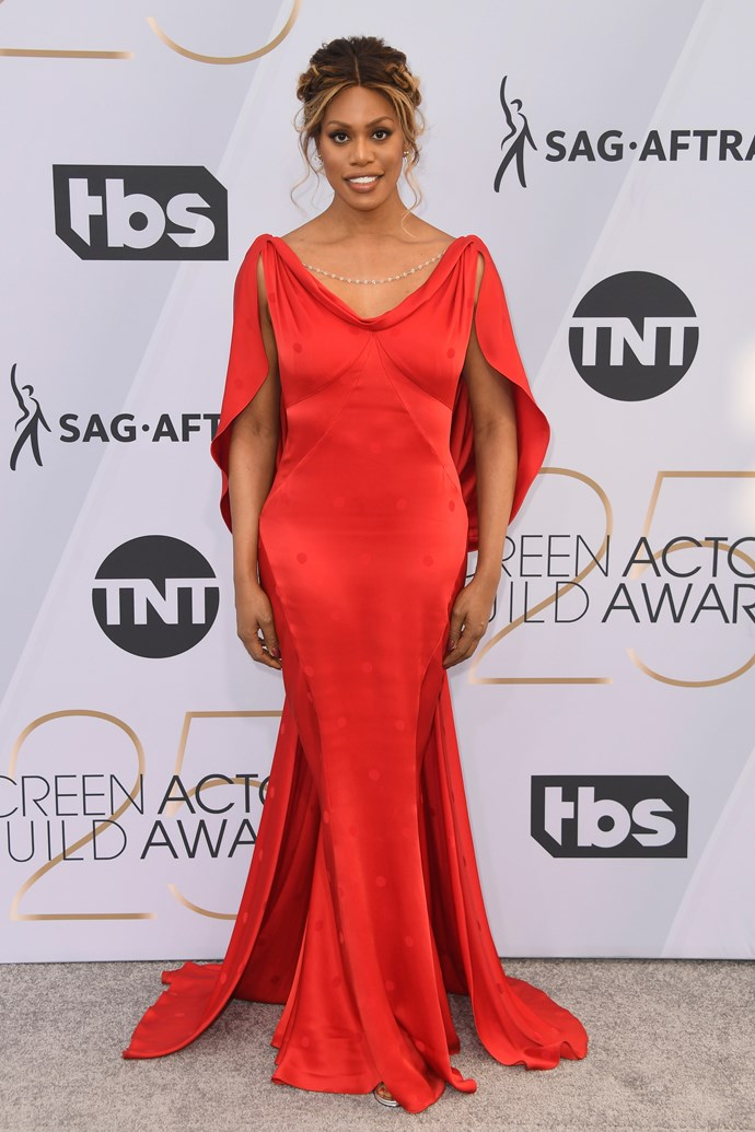 Laverne Cox brings a pop of colour in a flowing silk caped dress.