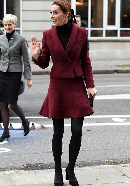 The ultimate winter inspiration - Kate's berry red skirt suit by Paule Ka is a statement in itself when paired with a black roll neck jumper and stockings. *(Image: Getty)*