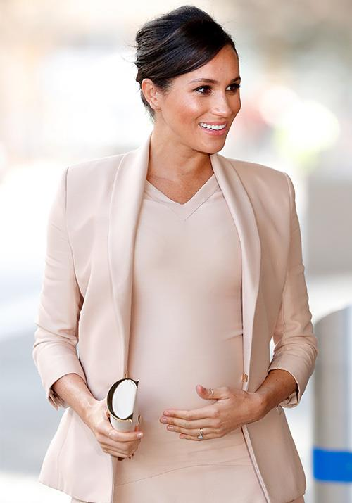 Duchess Meghan's baby bump was on full display as she visited the National Theatre in London. *(Image: Getty)*