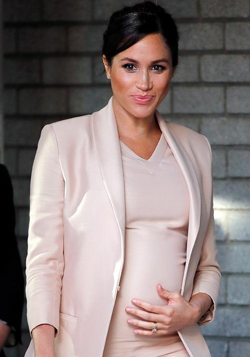 Meghan cradled her baby bump throughout the visit. *(Image: Getty)*