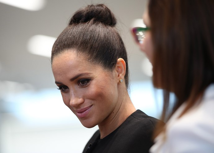 Meghan's trademark messy bun has been replaced with a more polished look. *(Image: Getty)*