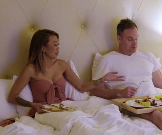 Mark and Ning sharing breakfast in bed together, the morning after their wedding. *(Image: Channel Nine)*