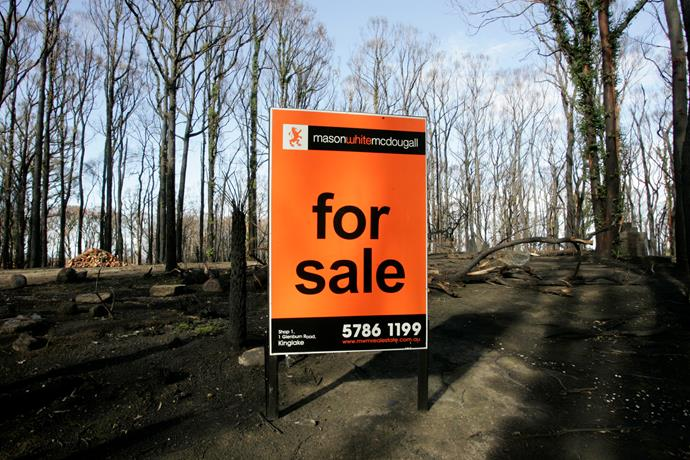 A for sale sign stands alone on a blackened property in Kinglake, six months after the Black Saturday bushfires. *(Image: Getty)*