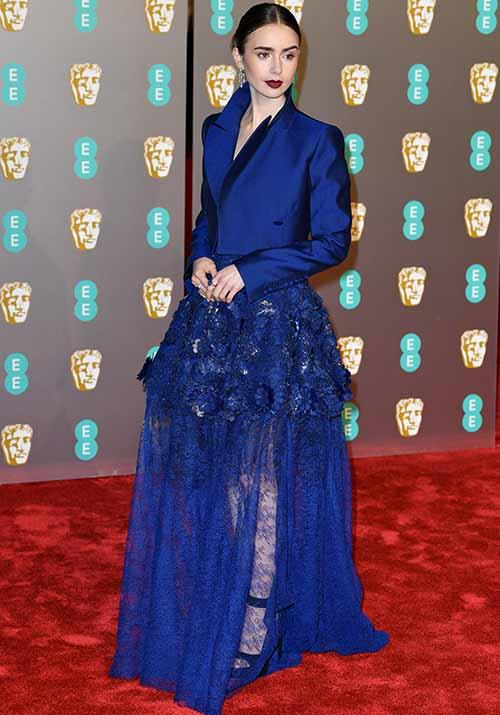 British actress Lily Collins knows how to make a statement - and this satin blazer and sheer skirt does all the talking. *(Image: Getty)*