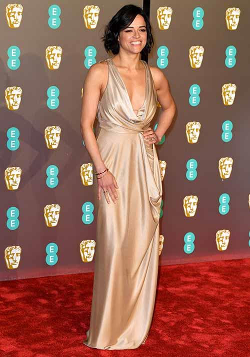 *Widows* actress Michelle Rodriguez opted for a chic golden gown. *(Image: Getty)*