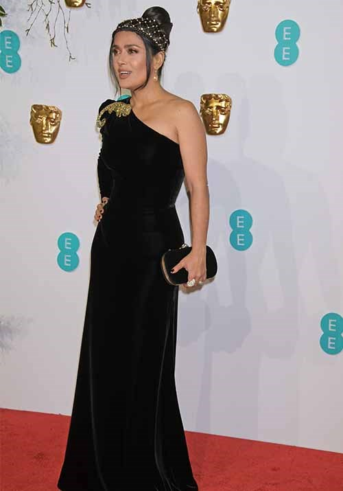 Salma Hayek opted for a simple black one-shoulder gown with gold detailing paired with a pearl-adorned headband. *(Image: Getty)*