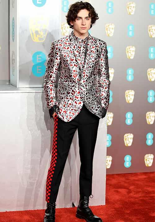 French-American actor Timothée Chalamet went for a daring look in a bold printed blazer paired with checked red and black pants. *(Image: Getty)*