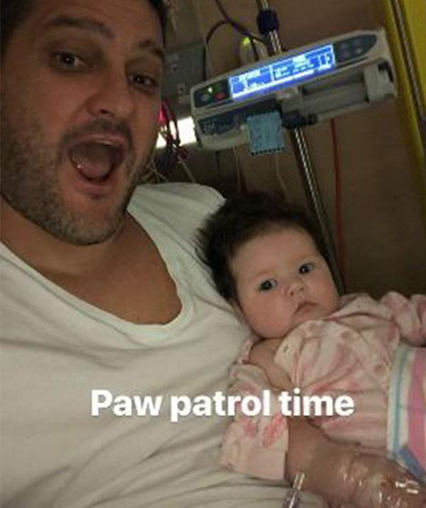 Brendan cuddles Tobi from her hospital bed. *(Image: @brendanfevola25 Instagram)*