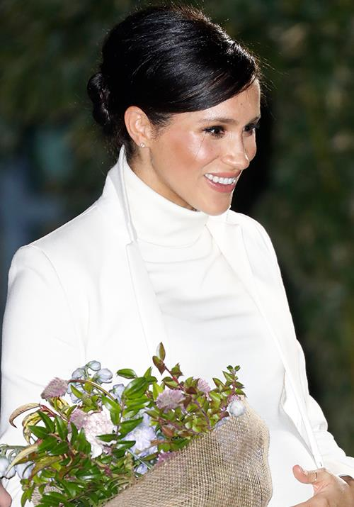 The Duchess was presented with a bunch of flowers as she greeted guests.  *(Image: Getty)*