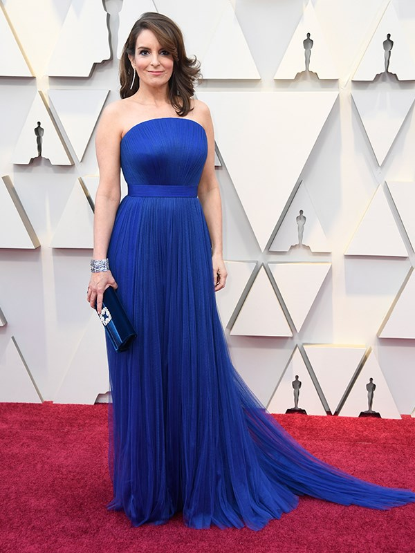 Meanwhile, Tina Fey embraces her femininity in a royal blue custom Vera Wang gown paired with sparkling silver jewellery.
