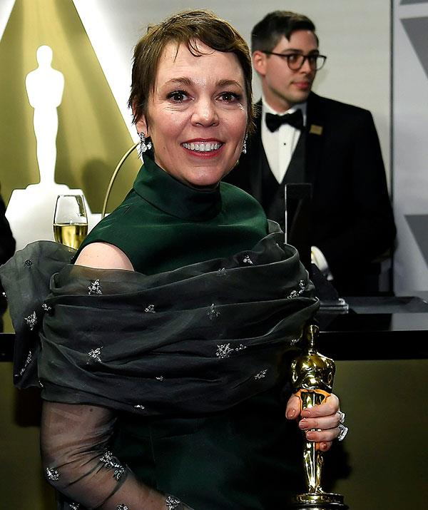 Best Actress winner Olivia Colman proudly showcases her sparkly new accolade at the Governors Ball. *(Image: Getty)*