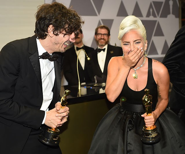 Still taking in her Best Song win, *A Star is Born* beauty Lady Gaga shares a laugh with Anthony Rossomando at the Governors ball at the Hollywood & Highland Center in LA. *(Image: Getty)*