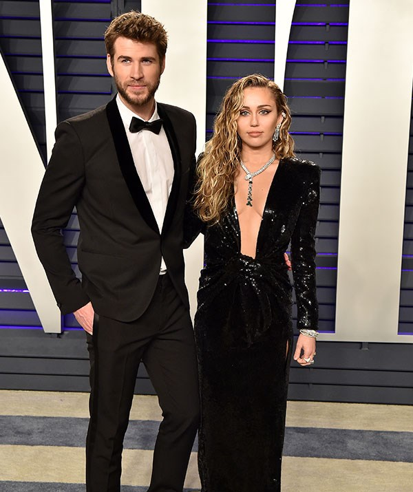 Miley dazzled in a plunging black dress, which she teamed with a serious serving of bling. While Liam cut a stylish figure in a black tux. *(Image: Getty)*