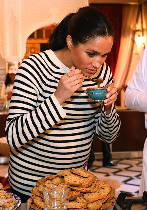 Meghan delighted in tasting some of the chef's delicacies. *(Image: Getty)*