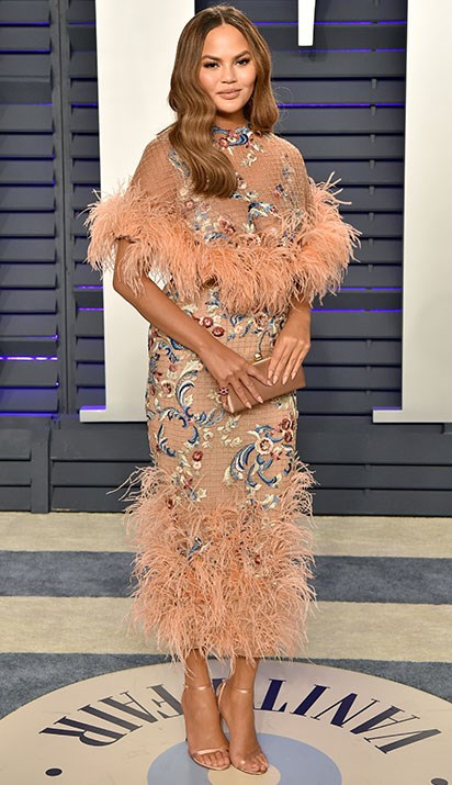 Chrissy's feathered peach frock is all kinds of chic. *(Image: Getty)*